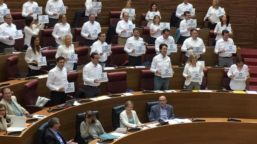 Los diputados del PP valenciano, con camisas blancas y un cartel en el que se lee 'Llibertat Educativa'