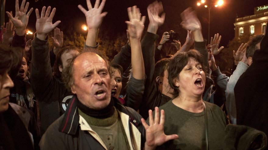 Manifestantes con las manos en alto frente a las vallas; se niegan a moverse a pesar de la intimidación policial. Alvaro Minguito