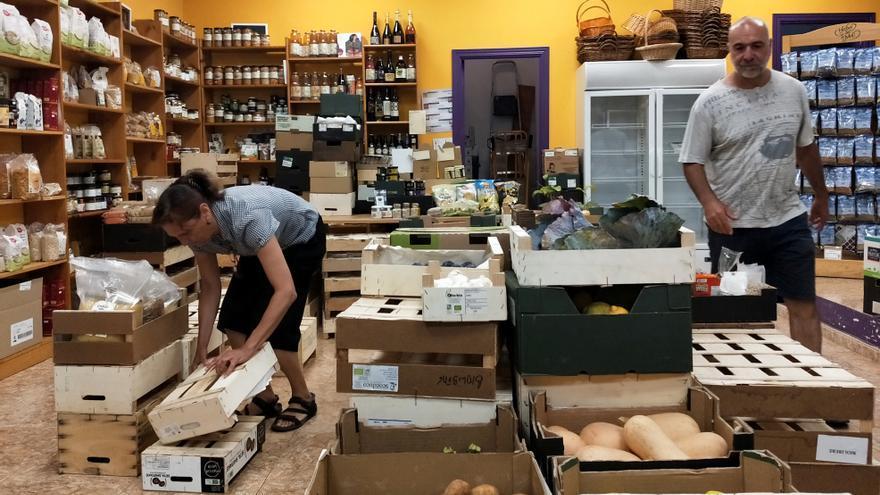 Lourdes López y Emilio Lázaro, dos socios de la tienda ecológica Biolíbere, en Getafe, acomodan el local.