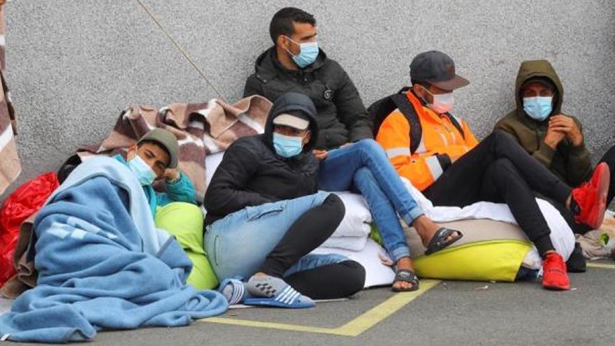 Un grupo de 64 inmigrantes duerme al raso, con mantas y cartones, tras abandonar un campamento en Gran Canaria