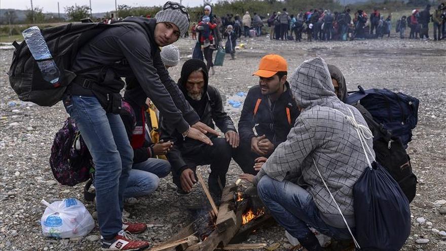 Varios refugiados se calientan junto a una hoguera en un centro de registro. Miles de refugiados continúan su travesía hacia los países de Europa por la ruta de los Balcanes. / Efe.