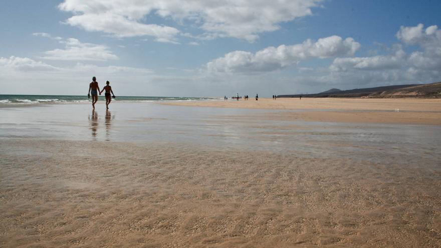 Una pareja pasea por la orilla de la Playa de Sotavento, en Fuerteventura.