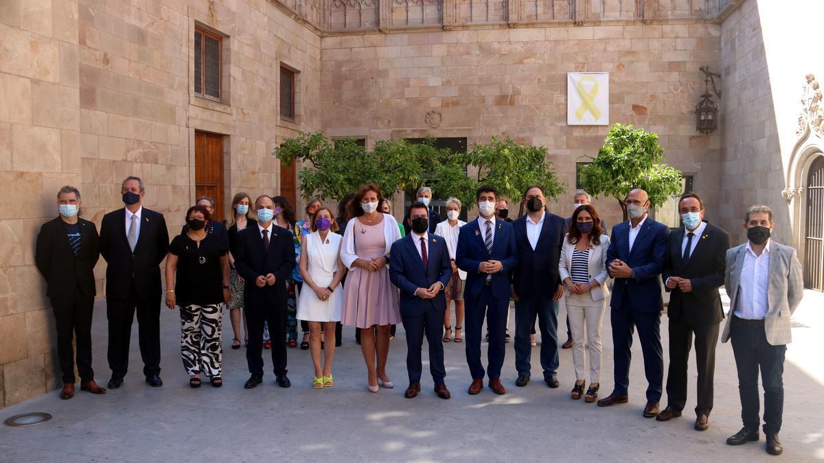 Los nueve presos indultados junto al Govern y la presidenta del Parlament, en el Palau