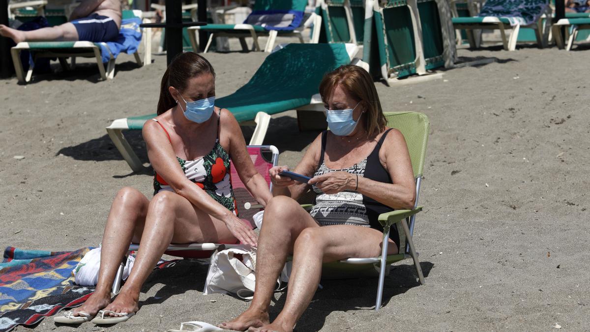 Dos mujeres con mascarillas en la playa