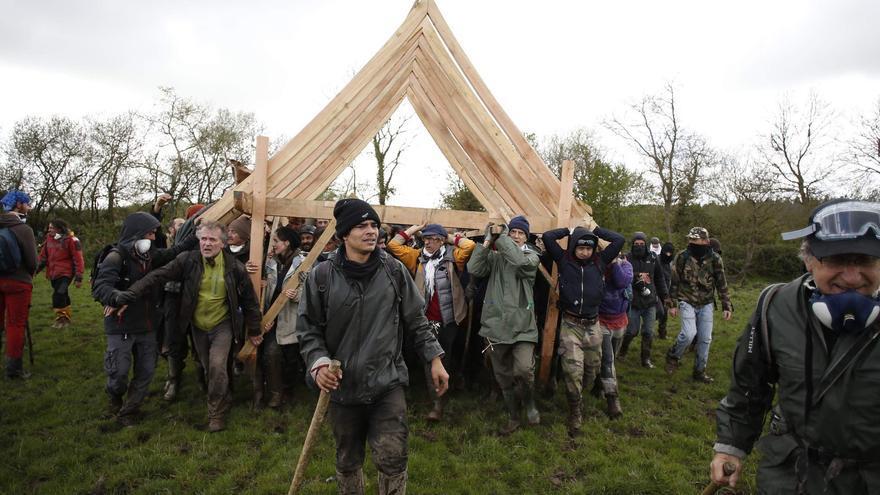 Decenas de personas portan una parte de la estructura de madera para la reconstrucción de Le Gourbi a través de toda la ZAD