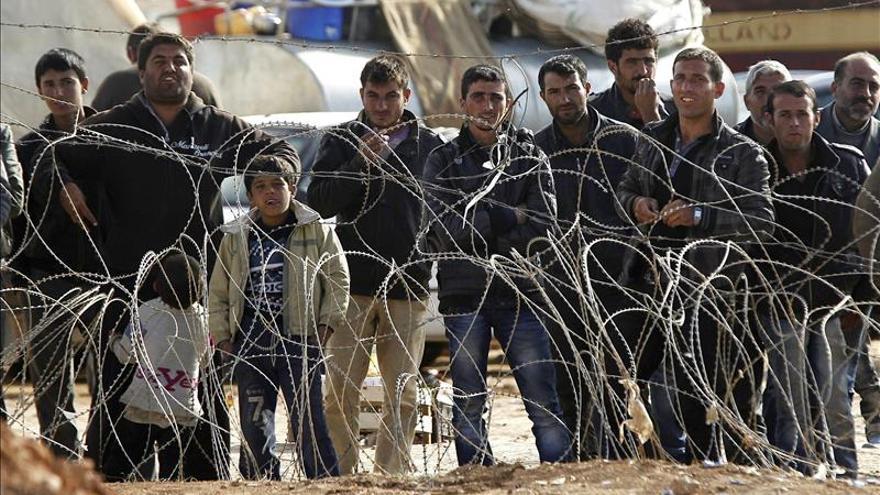 Refugiados sirios esperan para cruzar la frontera y pasar a Turquía cerca de Kobane (Siria).