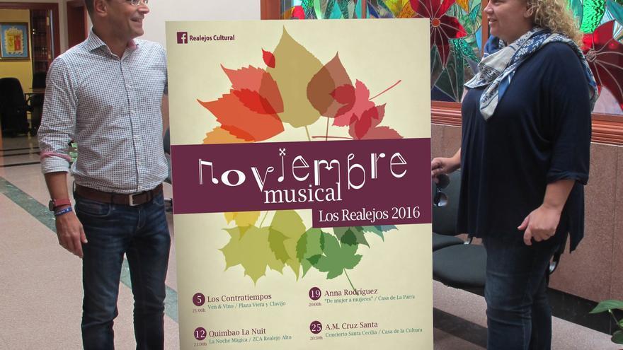 Dos concejales muestran el cartel con la programación