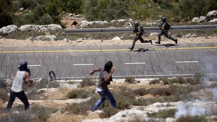 Dos palestinos tiran piedras contra soldados israelíes en Al Walaja durante las protestas por el 66 aniversario de la Nakba, en 2014