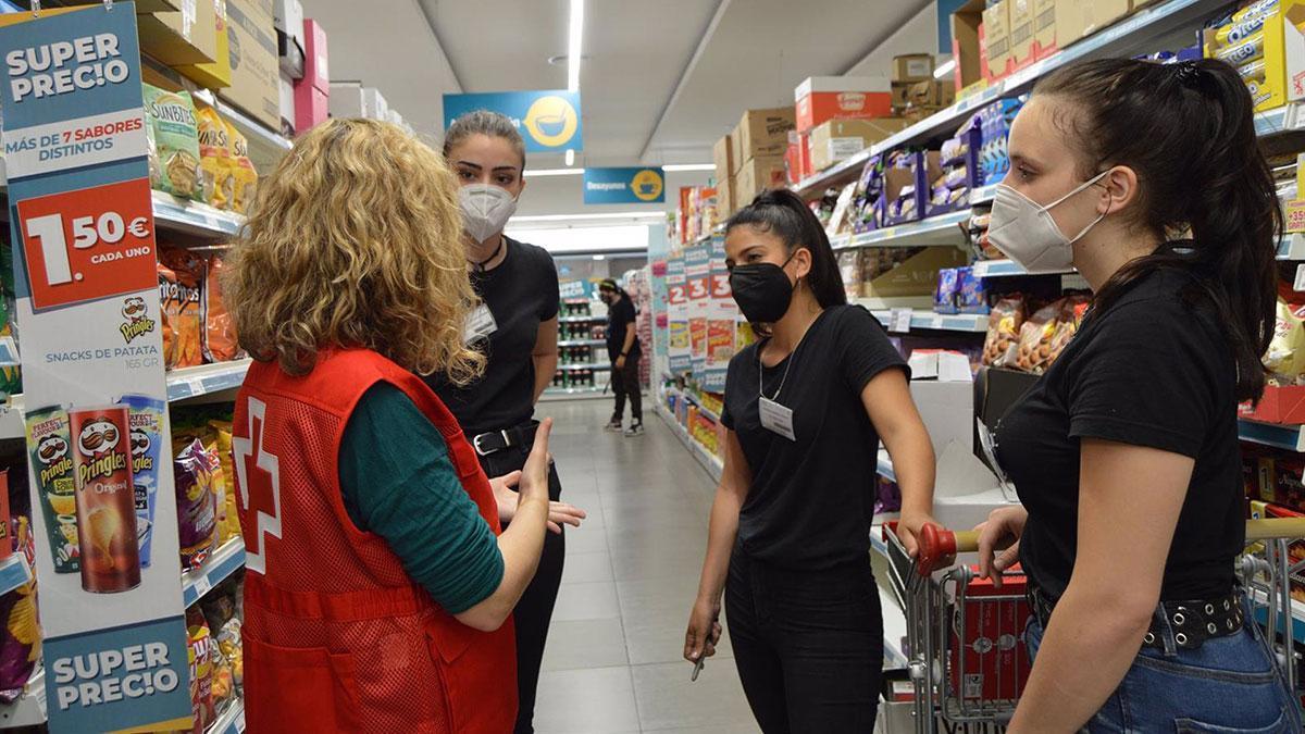 Una voluntaria de Cruz Roja junto a tres trabajadoras en un supermercado.