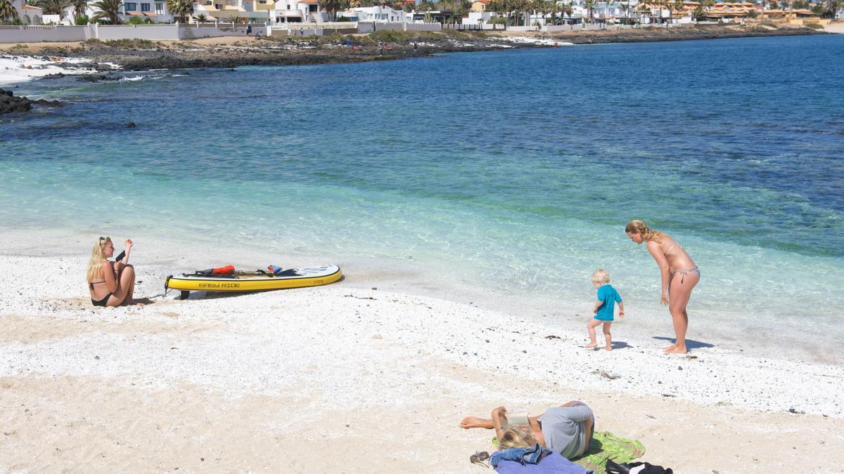 Turistas disfrutando de un día de playa en la localidad canaria de Corralejo, en el norte de Fuerteventura. EFE/Carlos de Saá/Archivo