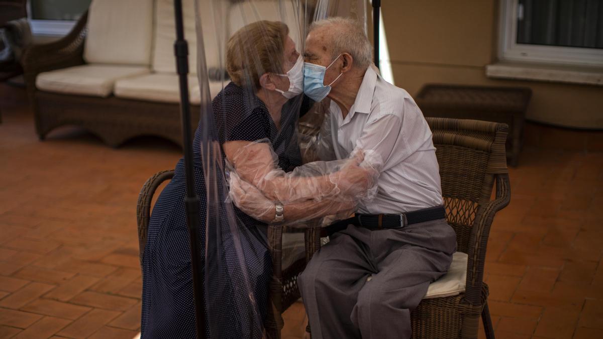 Agustina Canamero, 81, y Pascual Perez, 84, se abrazan y besan a través de una membrana de plástico para evitar contraer el coronavirus en una residencia de Barcelona, España el 22 de junio de 2020