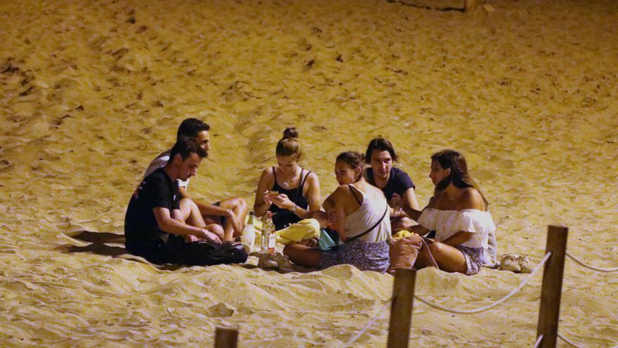 Un grupo de amigos haciendo botellón en la playa.