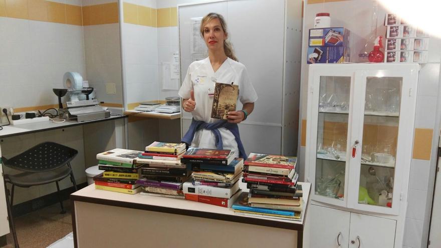 Olga Hernández muestra los libros que han sido donados hasta ahora.