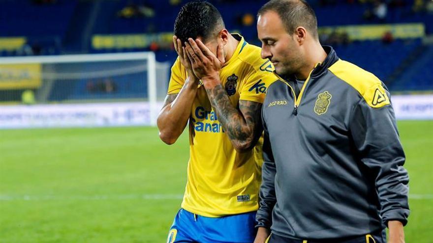 El centrocampista de la UD Las Palmas, Vitolo, abandona el terreno de juego acompañado del fisioterapeuta del equipo canario, Juan Naranjo. EFE / Quique Curbelo.