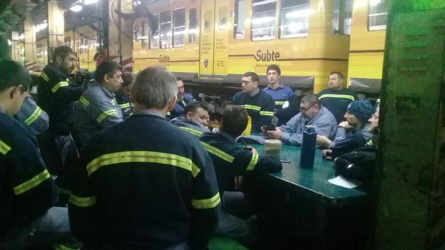 Trabajadores del metro junto a uno de los vagones de la red de metro de Buenos Aires, Subte