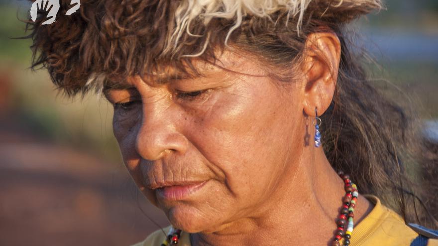 """Damiana pertenece a la tribu guaraní-kaiowá. Se piensa que este pueblo indígena fue uno de los primeros en ser contactados cuando los europeos llegaron a Sudamérica. Hubo una vez en que ocuparon una tierra de bosque y llanuras en Brasil que se expandía por 350.000 km cuadrados. Los guaraníes cazaban libremente en su hogar, y plantaban yuca y maíz en sus huertos. Sin embargo, durante el último siglo casi todo su bosque les ha sido robado y transformado en inmensas y secas parcelas de haciendas ganaderas, campos de soja y plantaciones de la prominente caña de azúcar. Hace una década, los terratenientes ganaderos intimidaron a Damiana y a su familia y la expulsaron de sus tierras ancestrales. Desde entonces, ha vivido en condiciones degradantes junto a una carretera. Su marido y tres de sus hijos han muerto atropellados. En septiembre de 2013, sin embargo, lideró una valiente y peligrosa """"retomada"""" (reocupación) de la plantación de caña de azúcar que ha invadido su tierra ancestral. Una retomada ha sido desde hace tiempo la esperanza y el consuelo de Damiana: la aspiración que la ha mantenido durante los brutales años de la expulsión, en medio del miedo, la humillación, la malnutrición, la pérdida, la enfermedad y la depresión. Hemos decidido luchar y morir por nuestra tierra, dijo Damiana./©Fiona Watson/Survival"""
