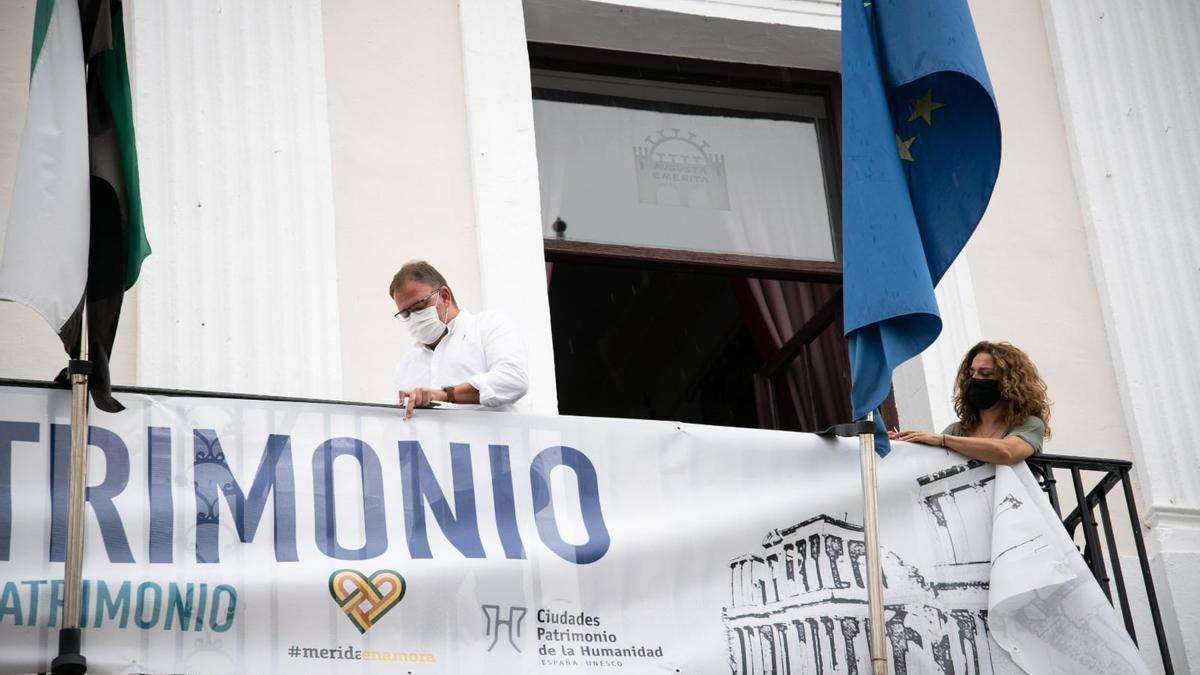 El alcalde de Mérida, Antonio Rodríguez Osuna, ha colocado esta mañana en el balcón del Ayuntamiento la pancarta de La Noche del Patrimonio