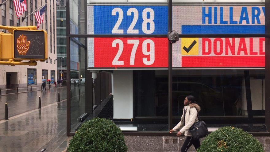 Una mujer, en una calle de Nueva York en la jornada posterior a las elecciones presidenciales de Estados Unidos, con los resultados de fondo. | FOTO: Juan Luis Sánchez.