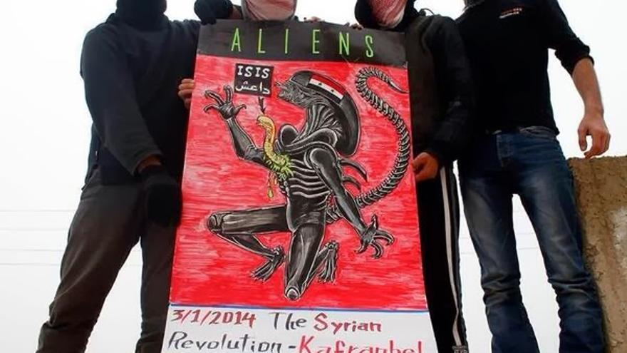Jóvenes de Kafranbel sostienen un cartel que representa al Estado Islámico de Irak y Siria saliendo de las tripas del régimen sirio. Fuente: Página oficial de Kafranbel