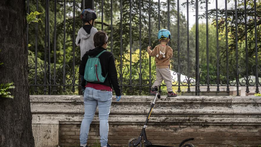 Una mujer y dos niños en el primer día de alivio del confinamiento de los menores.