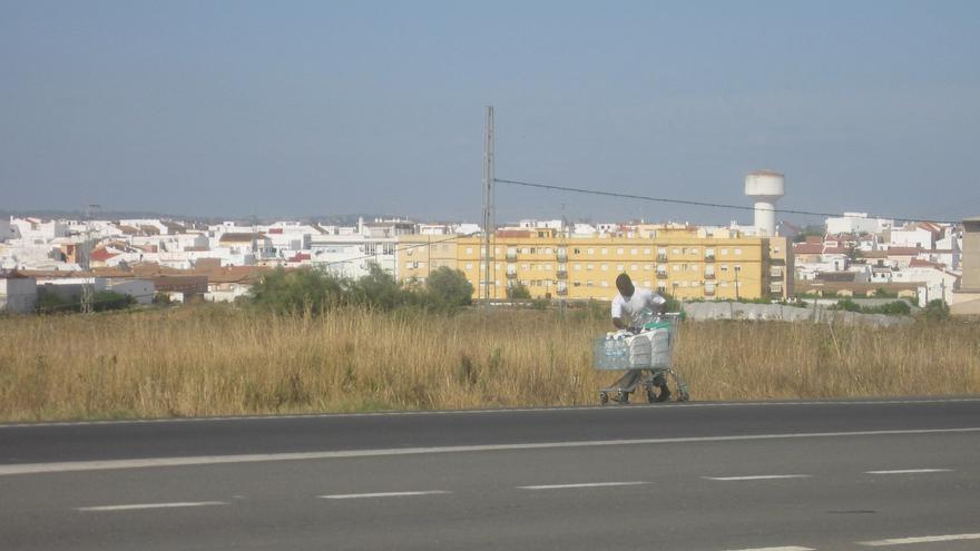 Un inmigrante transporta agua a su campamento por el arcén de una carretera, con edificaciones de Lepe de fondo.