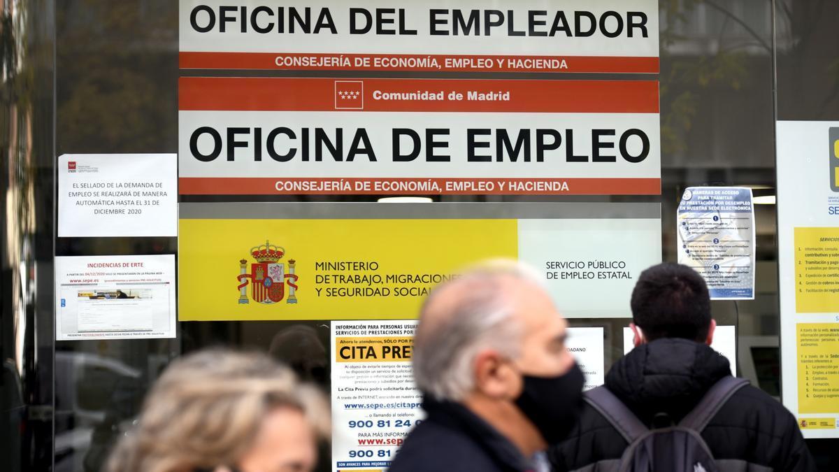 Varias personas en la puerta de una oficina de empleo, SEPE, en Madrid (España).