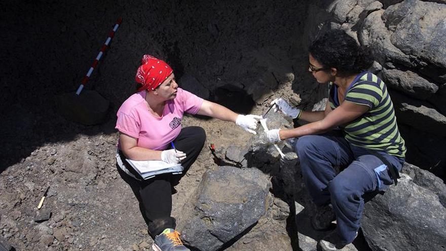 Las arqueólogas Rosa Lopez (d) y Verónica Alberto clasifican los huesos en el lugar del enterramiento. EFE/Carlos de Sáa