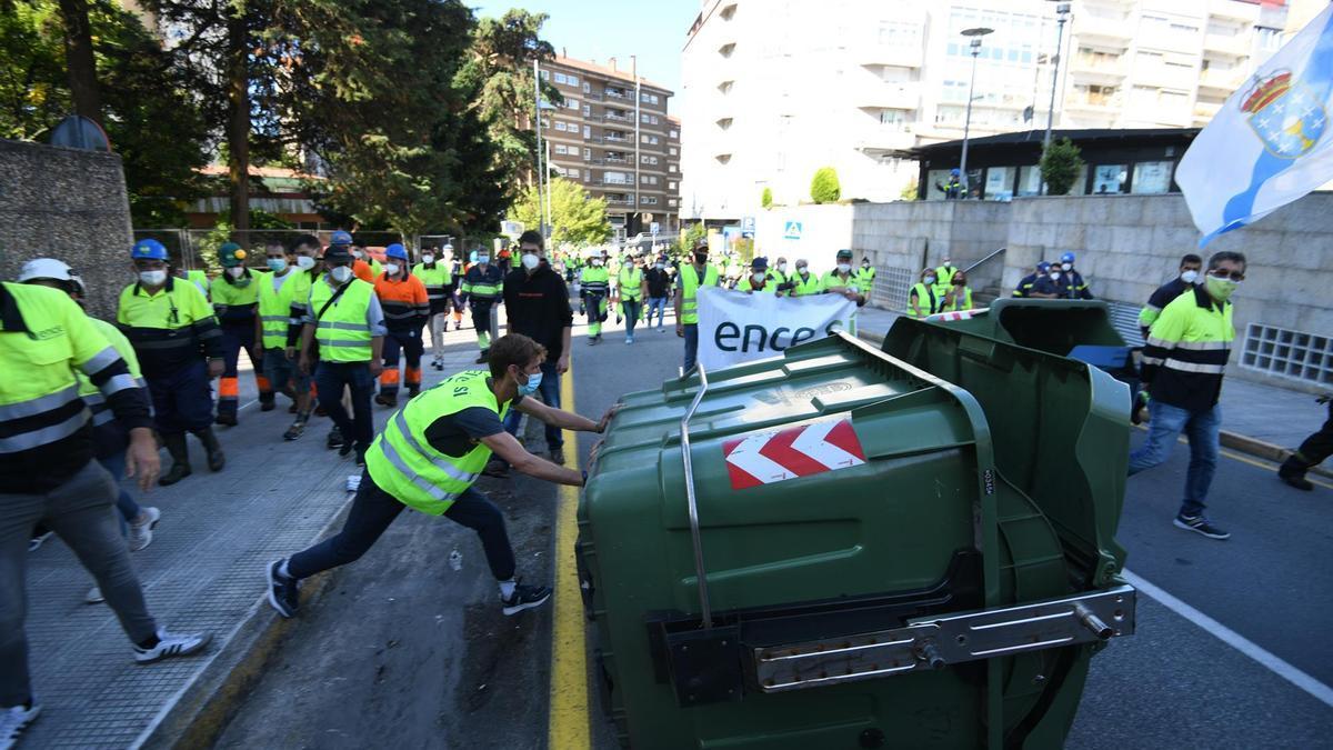 Un trabajador de Ence vuelca un contenedor durante las protestas