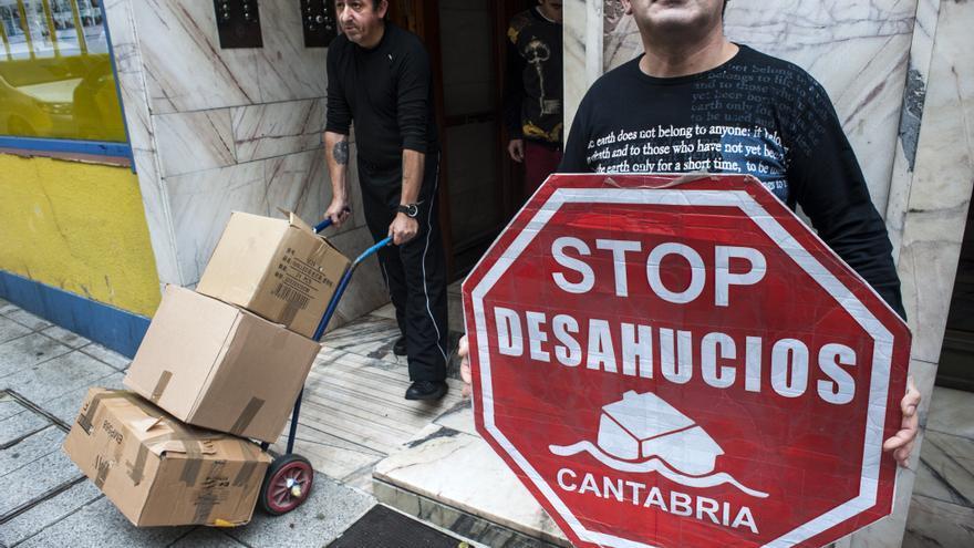 Luis, en el portal de la vivienda, sacando en cajas las pertenencias de la familia.   Joaquín Gómez Sastre