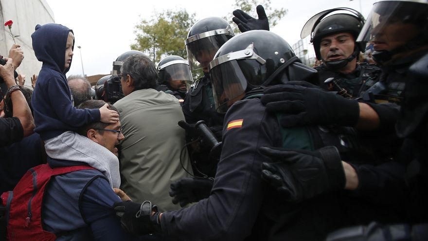 Civil guards clear people away from the entrance of a sports center, assigned to be a polling station by the Catalan government and where Catalan President Carles Puigdemont is expected to vote, in Sant Julia de Ramis, near Girona, Spain, Sunday, Oct. 1, 2017. Catalan pro-referendum supporters vowed to ignore a police ultimatum to leave the schools they are occupying to use in a vote seeking independence from Spain.