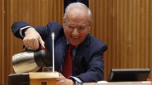 Alfonso Guerra se sirve agua en la presentación de su libro en el Congreso.