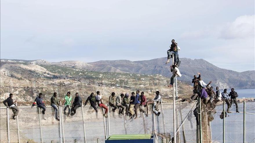 Imagen de archivo. Cerca de 25 personas de origen subsahariano permanecen encaramados durante horas en la valla de Melilla