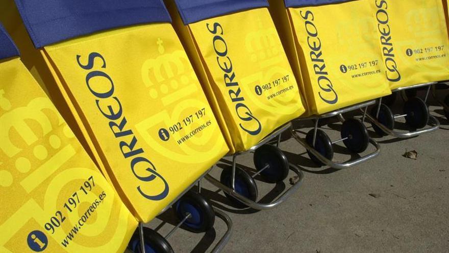 Carros de reparto de correo con el logo de la empresa CORREOS.