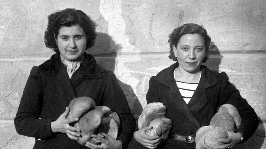 Dos muchachas transportan a sus hogares varias hogazas de pan repartidas por un camión de Auxilio Social. Enero de 1939 /EFE