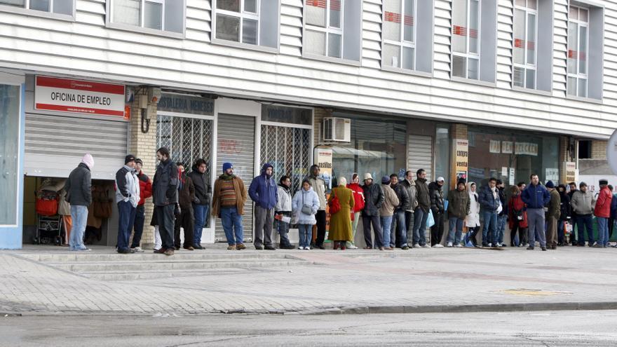 Varias personas formando cola ante una oficina del INEM. EFE