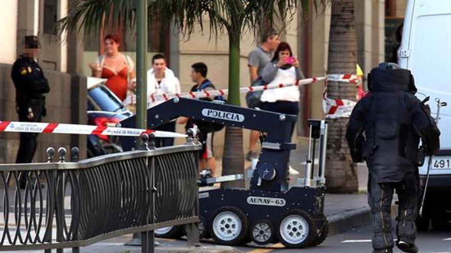 Un agente de los artificieros de la Policía Nacional junto al robot que hoy fue desplazado al parque San Telmo de Las Palmas de Gran Canaria tras ser detectado un paquete sospechoso abandonado bajo una papelera. Las precauciones adoptadas obligaron a cordonar la zona y a restringir temporalmente el tráfico en ese punto. EFE/Elvira Urquijo A.