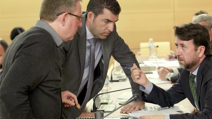 El presidente del Cabildo de Tenerife, Carlos Alonso (d), conversa con los portavoces del PP, Manuel Domínguez (c), y de Podemos, Fernando Sabaté, durante la sesión plenaria / Cristóbal García/EFE