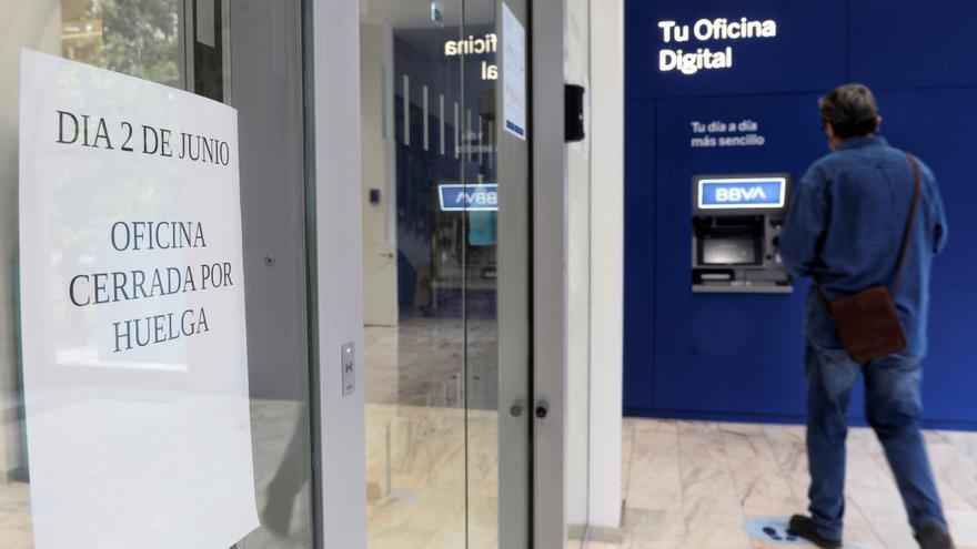 Un hombre se dispone a sacar dinero en un cajero automático en la oficina principal del BBVA, debido al cierre de esta por la huelga convocada este miércoles para protestar por los despidos que plantea esta entidad bancaria a nivel nacional.