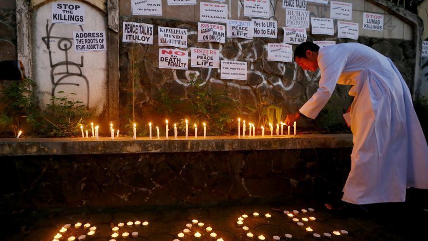 """Un cura enciende una vela frente a un muro con eslóganes contra la """"guerra contra las drogas"""" iniciada por el presidente, Rodrigo Duterte. 22 de febrero de 2017. AP Photos/ Bullit Márquez"""