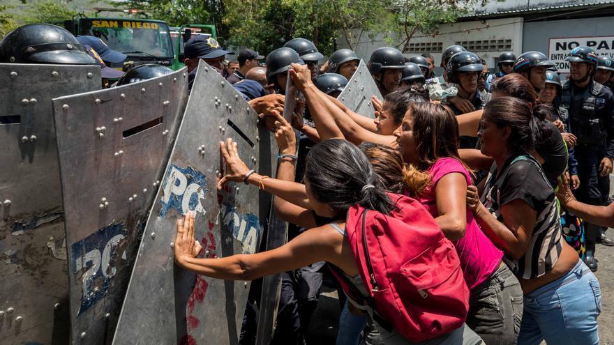 Un grupo de familiares de presos protesta ante miembros de la Policía en las inmediaciones del centro de reclusión de la Policía Estatal de Carabobo (centro) en Valencia (Venezuela).