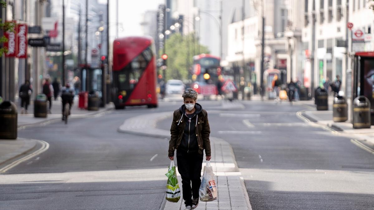 Una mujer volviendo de la compra en Londres (Reino Unido).