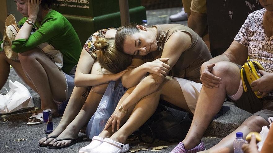 Varias mujeres sentadas en un bordillo en la calle en la noche del atentado en Barcelona este 17 de agosto.