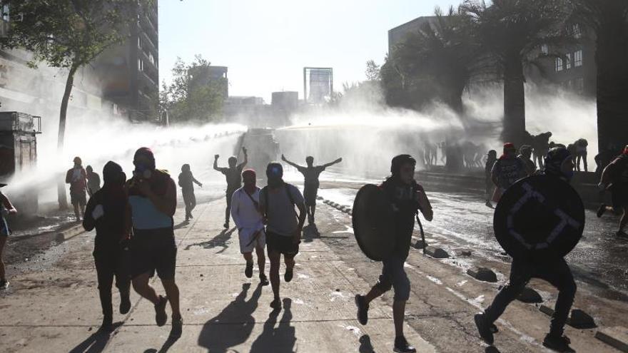 Grupo de manifestantes huyen del carro lanza aguas de la policía antidisturbios, durante una protesta contra del Gobierno del presidente Sebastián Piñera el 10 de enero de 2020 en la plaza Italia de Santiago (Chile).