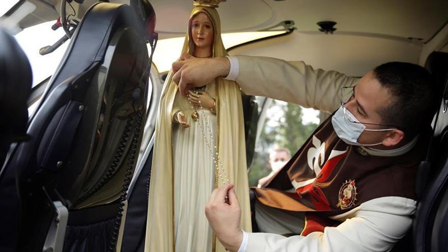 Un miembro de la congregación Heraldos del Evangelio coloca un rosario a una imagen de la Virgen de Fátima a bordo de un helicóptero este miércoles, en San Salvador (El Salvador). La imagen de la Virgen de Fátima recorrió en helicóptero diferentes ciudades de El Salvador debido a la suspensión de eventos públicos y aglomeraciones por la pandemia de COVID-19.