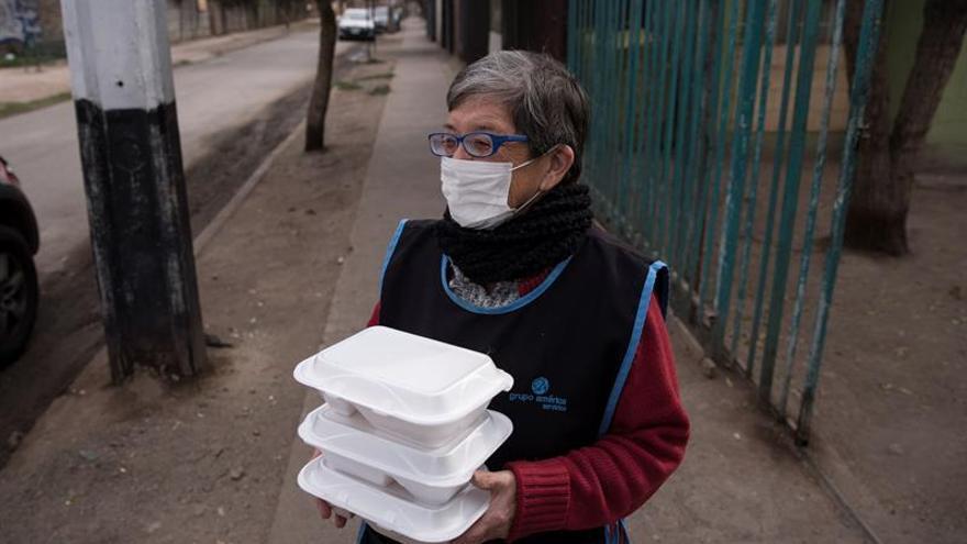 Una vecina de la comuna de Puente Alto fue registrada estes martes al recibir cajas con comida, en la comuna de Puente Alto, en Santiago de Chile.
