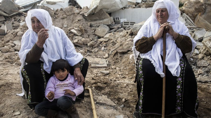 Los aldeanos palestinos se sientan sobre los restos de sus casas derruidas por los israelíes/ (c) Peter Beaumont/ / The Guardian