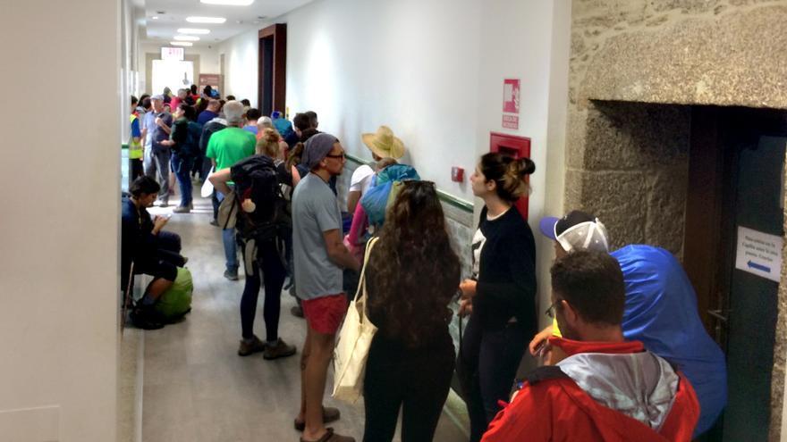 Peregrinos hacen cola para recoger su 'Compostela' en la Oficina del Peregrino tras llegar a Santiago