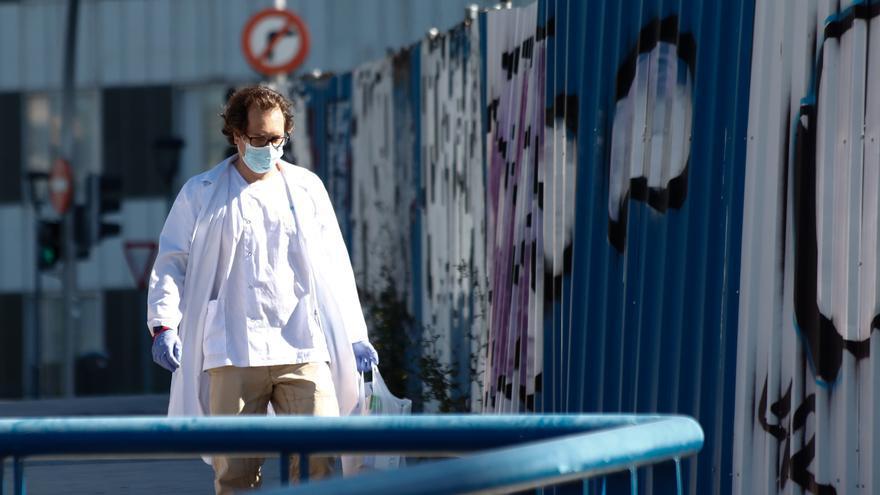 Un sanitario con bata y mascarilla en la puerta de un hospital de Madrid. / Óscar J.Barroso EP