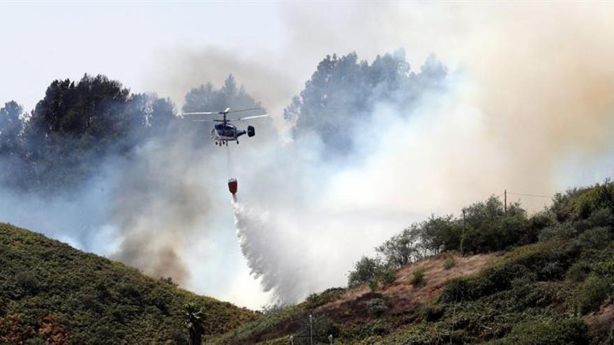 Uno de los nueve helicópteros que trabajan en las labores de extinción del incendio forestal en la localidad de Montaña Alta. EFE/Elvira Urquijo A: