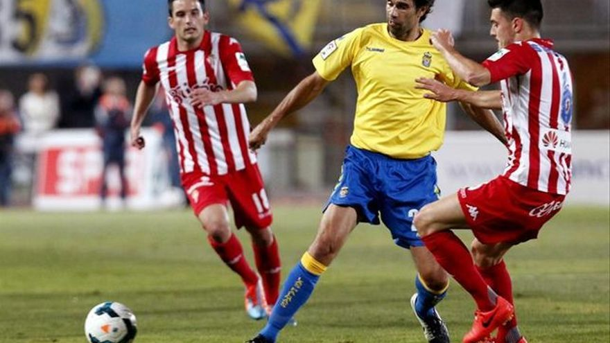 El centrocampista de la UD Las Palmas Valerón (c) trata de escapar entre Sergio (i) y Lora, ambos del Sporting de Gijón, durante el partido de ascenso a Primera División disputado en el estadio de Gran Canaria, en Las Palmas. EFE/Elvira Urquijo A.